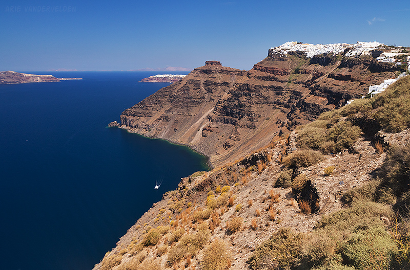 Looking ahead along the crater rim. The town in the top-right is Imerovigli, and the town in the far distance is Oia.