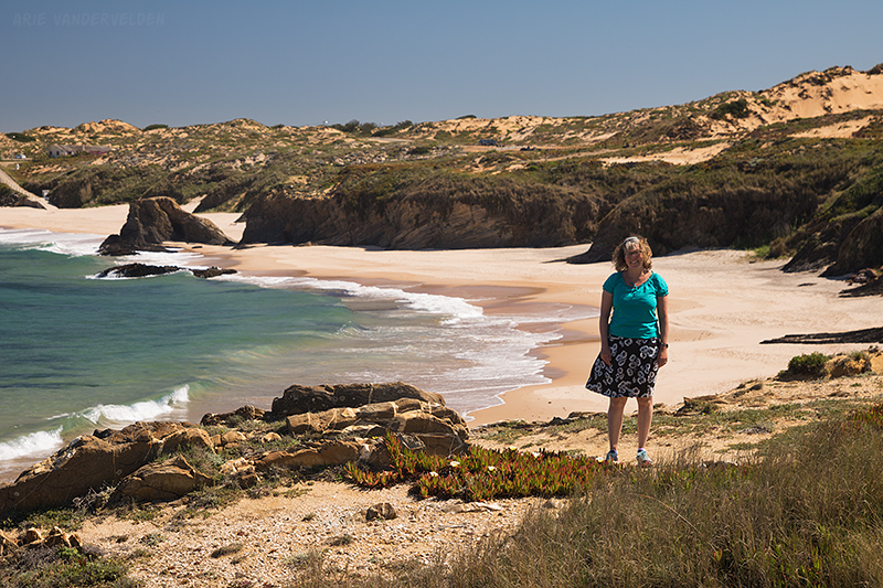 Looking back at Diana at Praia de Almogarve. Note the rocks with the gap in the middle, which split the beach in two.