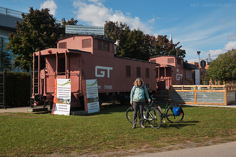 Diana at the finish line. The bike rental / shuttlebus company has its office in an old caboose.